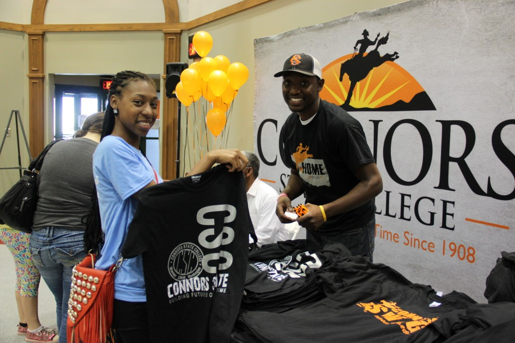 Connors State College Recruiter Spencer Nero offers a free T-shirt to Ravene Bolden who was seeking degree information at a recent Open House.  Connors will host a second Open House on the Warner campus in the Fine Arts building on Sat., July 12, from 11 a.m. to 2 p.m.