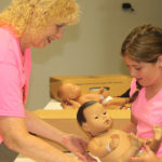 CSC's Eileen Thomas shows Babysitter Boot Camp participant Bailee Coltharp, 10, of Ft. Gibson, how to change a diaper.